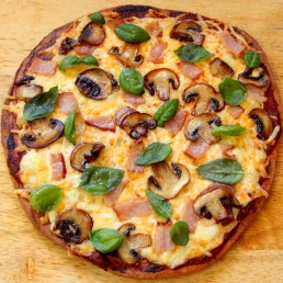 Fathead Pizza Crust lying on a wooden table with ham and mushrooms